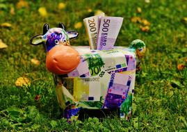 Piggy Bank on lawn, toy Cow with bills in hole