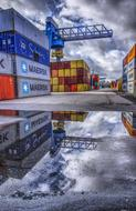stack of shipping Containers in Port mirroring on puddle