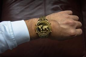 Cryptocurrency symbol on clock face of wrist watches on male hand