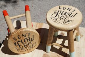 don't grow up, it's a trap, writing on wooden stools