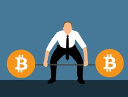 businessman holds barbell with bitcoin symbols