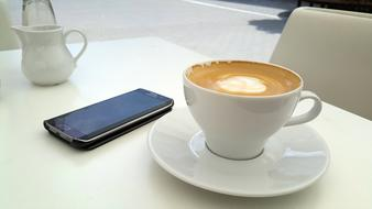 smartphone and a cup of coffee on a table in a restaurant