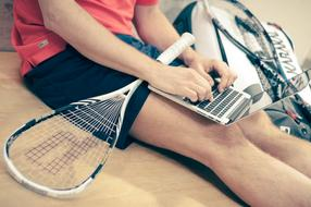 man sits on floor with Tennis racket and laptop