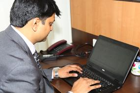 man works with laptop at desk