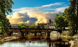 stone Bridge across calm River in old city, france