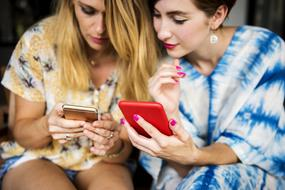 two young women sit Together looking at Phones