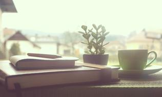 Coffee and Notebook on Wooden window sill in countryside