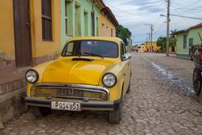 Yellow Old Car parked in the street at one-storey building, Cuba