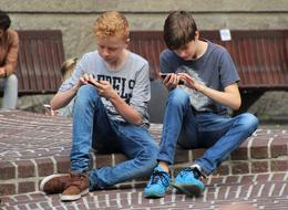 teens play on the phone and look for Pokemon in the street