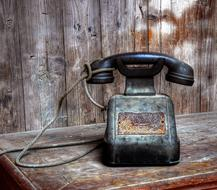 black retro telephone on a wooden bench
