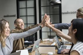 Achievement of Agreement, four young people making high five hand gesture in office