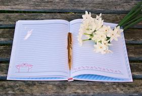 a bouquet of bouillon flowers and a pen lie on an open notebook