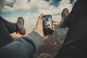 person with smartphone in hand above mountains