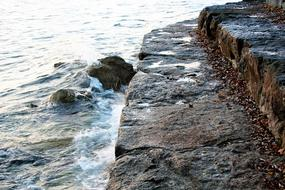 weathered wet stone steps at water