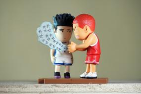 asian and caucasian sportsmen, two funny toy figurines