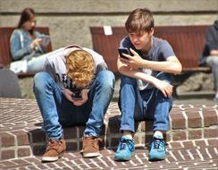 two students play pokemon go on a city street
