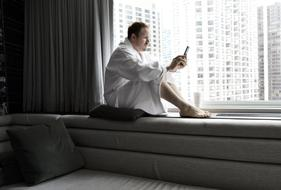 photo of a man in a white coat sitting on a windowsill