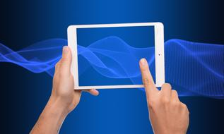 Tablet Computer in hands at abstract blue background