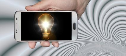 shining vintage light bulb on screen of smartphone