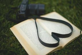 Photo camera strap in heart shape on open book