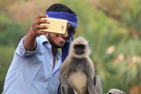 young Boy taking Selfie With Monkey