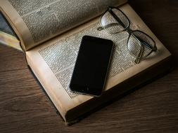 glasses and a smartphone lie on an open book