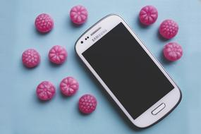 pink candy and samsung galaxy on the table