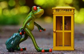 ceramic frog with luggage and telephone booth