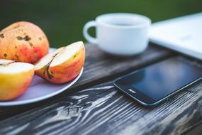 cup of coffee, smartphone and garden apples on a wooden table