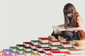 painted reading girl sitting on a pyramid of books