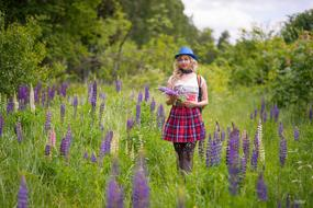 photo of a girl in a blue hat on a lupine field