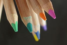 wooden colored pencils on the black background