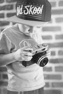 black and white photo of a child with a camera