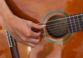 person's hand on strings of acoustic guitar