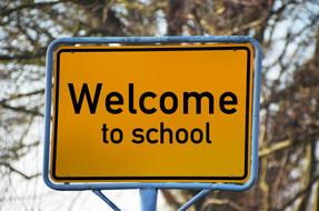 road sign town sign welcome school