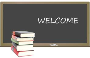 welcome, writing on black board, and stack of books