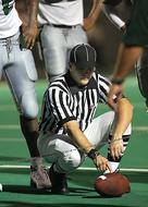 football referee holding the ball on the field