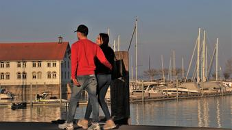young couple in love walks in the harbor in the evening