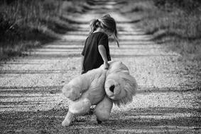black and white photo girl drags a teddy lion along a country road