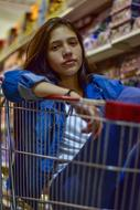 Young Woman with shopping cart in supermarket