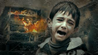 photo of a crying boy on a background of a burning house