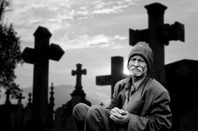 black and white photo of an elderly man in a cemetery