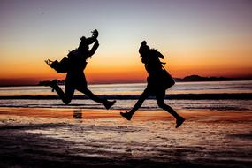 photo of two jumping people on the evening beach