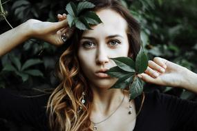 photo portrait of a girl among dark green leaves