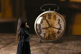 photo of a girl in a black dress on a background of an alarm clock