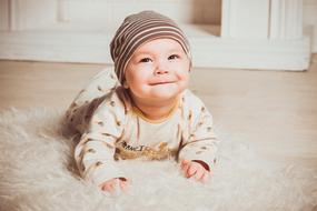 cute newborn lies on a fluffy carpet