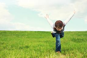 boy depicts a plane on a green meadow