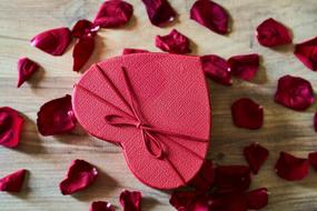 red heart-shaped box and rose petals on the table