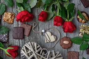 chocolates, a bouquet of roses and a wicker heart on the table