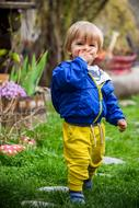 happy child in a blue jacket and yellow pants